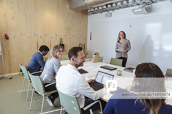 Smiling male and female business colleagues sharing ideas in office meeting