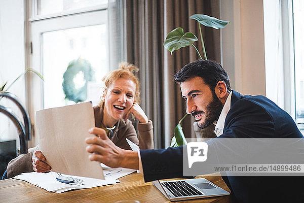 Lächelnde weibliche Illustratorin zeigt einem männlichen Unternehmer im Büro eine Zeichnung