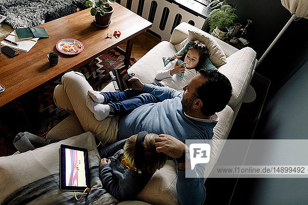 High angle view of father and daughters using various technologies on couch in living room at home