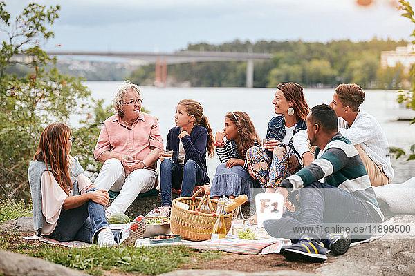 Familie und Freunde betrachten ältere Frau  während sie am Seeufer im Park sitzen