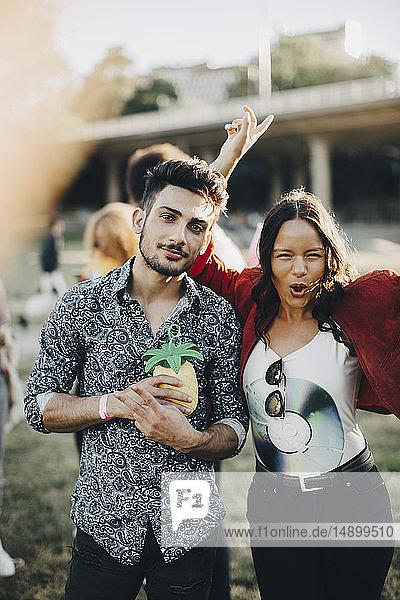 Porträt einer tanzenden Frau  die im Konzert mit einem Freund steht und etwas trinkt