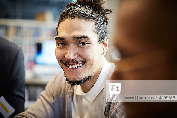 Portrait of smiling creative businessman sitting by male in office