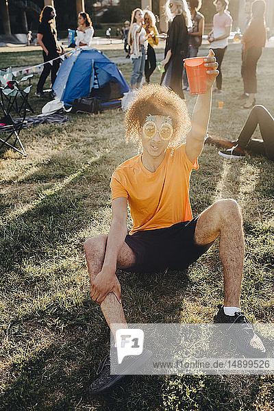Porträt eines Mannes  der während eines Musikfestivals im Gras sitzend trinkt