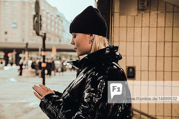 Seitenansicht einer jungen Frau  die ein Mobiltelefon benutzt  während sie im Winter am Eingang der U-Bahn in der Stadt eine schwarze glänzende Jacke trägt