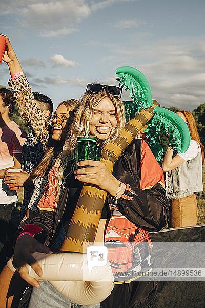 Glückliche Frau hält Ballon in der Hand  während sie mit Freunden beim Musikfestival einen Drink genießt