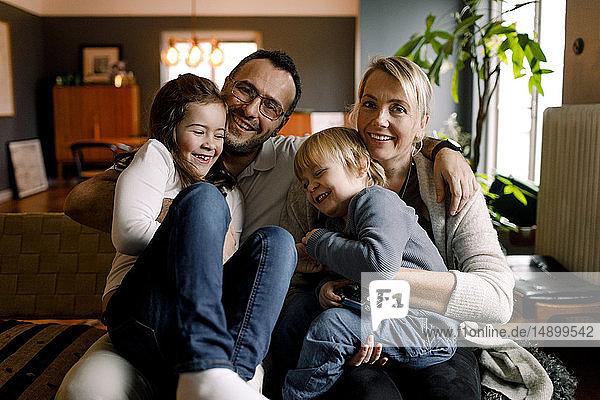 Porträt von Eltern mit fröhlichen Töchtern  die zu Hause im Wohnzimmer sitzen