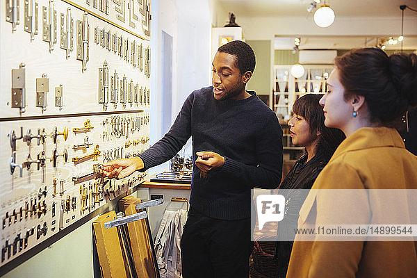 Junger männlicher Verkäufer zeigt weiblichen Kunden  die im Baumarkt stehen  Metallverschlüsse