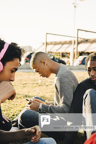 Male friends sitting on field during sunny day