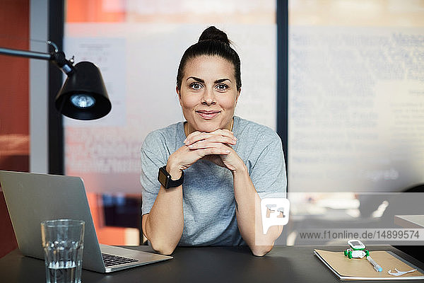 Portrait of confident creative businesswoman sitting at desk in office