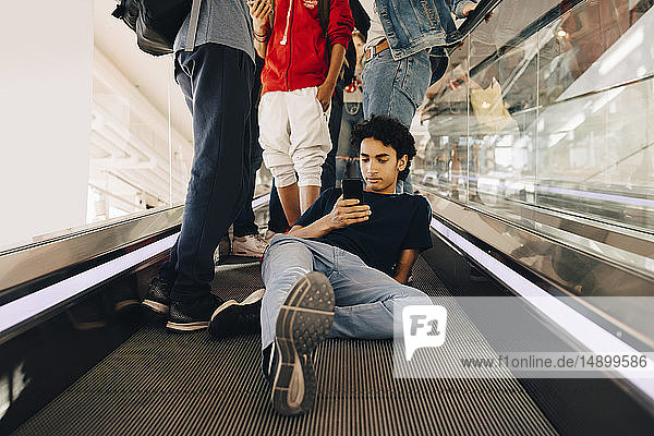 Teenage boy using mobile phone while sitting by friends on moving walkway in shopping mall
