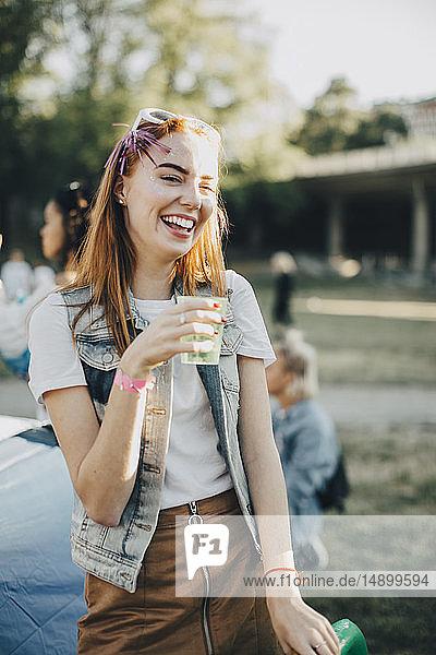 Fröhliche Frau trinkt im Stehen auf Rasen beim Musikfestival