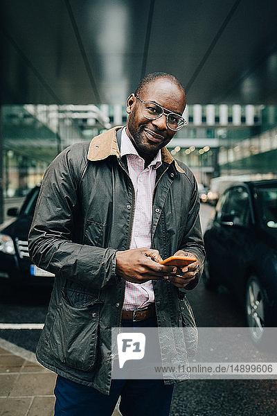 Porträt eines Geschäftsmannes  der ein Smartphone benutzt  während er auf der Straße gegen Gebäude in der Stadt steht