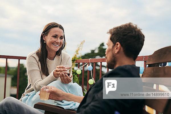 Fröhliche Frau unterhält sich mit einem männlichen Freund  während sie während des geselligen Beisammenseins auf der Terrasse ein Getränk hält