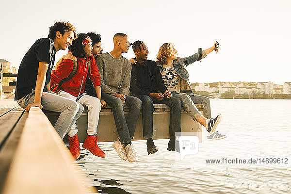 Happy male friends taking selfie while sitting side by side on pier by river