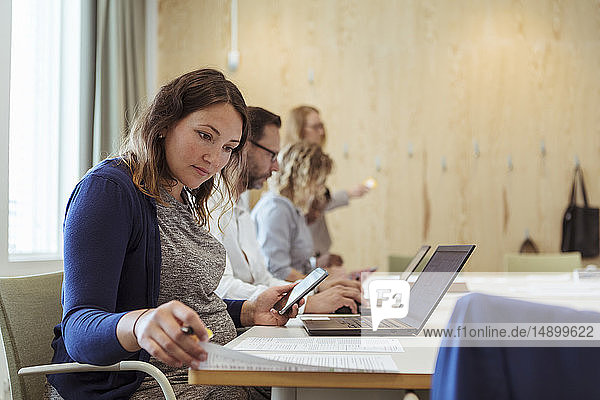 Pregnant businesswoman with smart phone and laptop reading document in office meeting