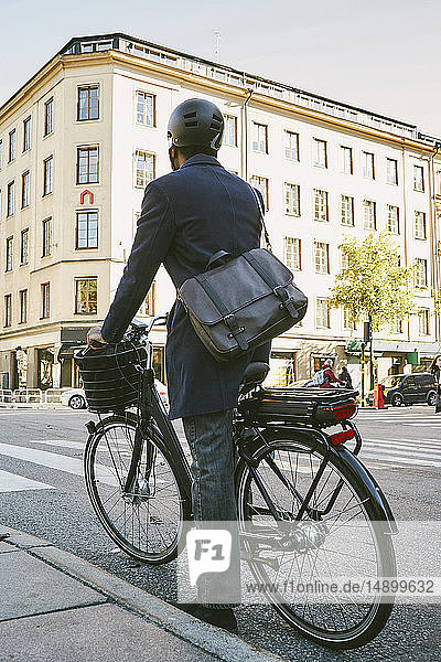 Rear view of male commuter riding electric bicycle on street in city