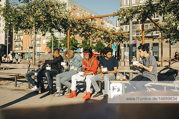 Male friends eating take out food while sitting side by side on bench in city