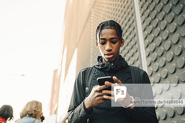 Low angle view of teenage boy using mobile phone while standing in city