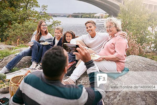 Mann fotografiert glückliche Familie beim Essen auf einem Felsen im Park während eines Picknicks