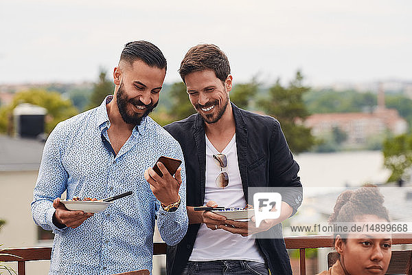 Smiling man showing mobile phone to friend while holding meal during party on terrace