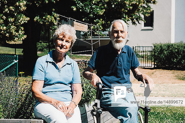Portrait of smiling retired senior man and woman sitting at back yard