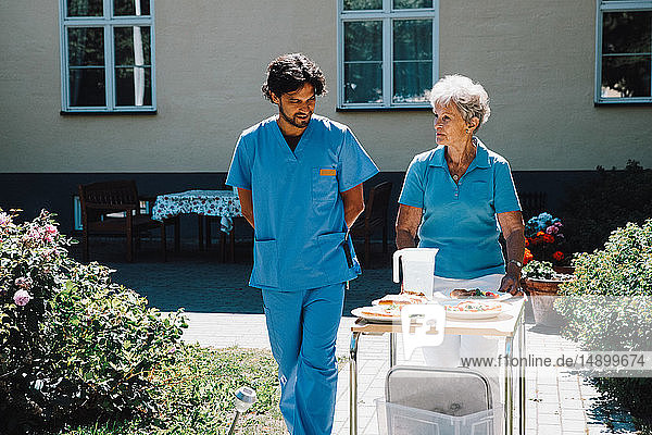 Male nurse walking with senior woman pushing food cart against nursing home