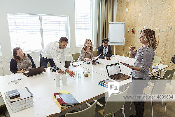 Businesswoman giving presentation to colleagues at conference table in meeting