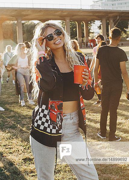 Verspielte glückliche Frau mit Getränk stehend beim Musikfestival