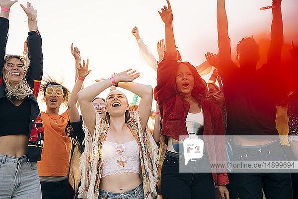Fröhliche Fans  die im Sommer mit gegen den Himmel erhobenen Armen schreien