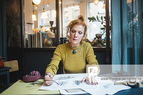 Confident mature female illustrator drawing on paper at desk in creative office