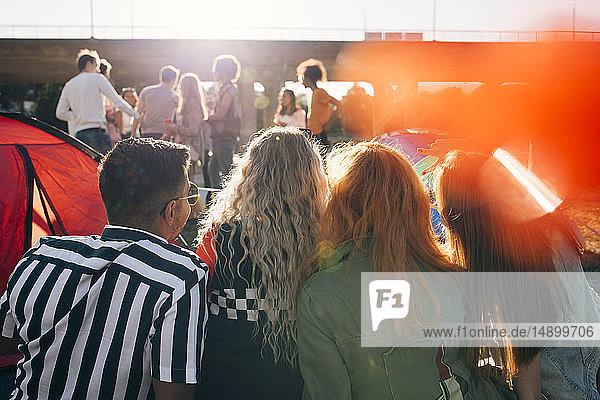 Rückansicht von Freunden  die beim Betrachten von Musikdarstellern sitzen Rückansicht von Freunden, die beim Betrachten von Musikdarstellern sitzen