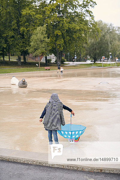Rear view of girl wearing raincoat playing with umbrella in park during rainy season