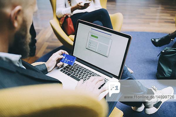 Schrägaufnahme eines Geschäftsmannes  der eine Kreditkarte hält  während er seinen Laptop am Flughafen benutzt
