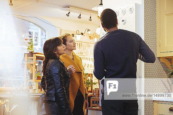 Junger männlicher Verkäufer zeigt weiblichen Kunden  die im Baumarkt stehen