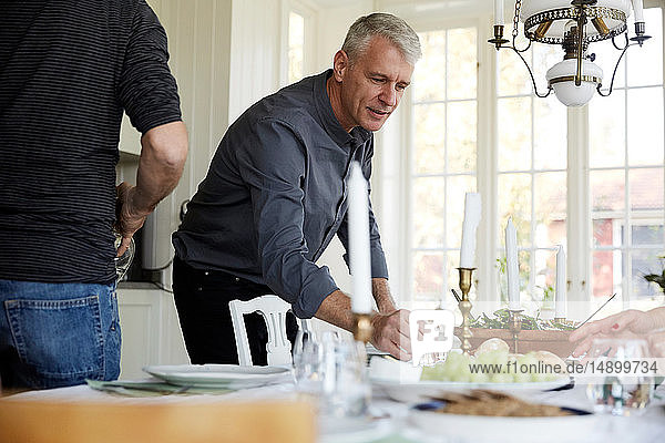 Mature man holding drinking glass on dining table by friend at home