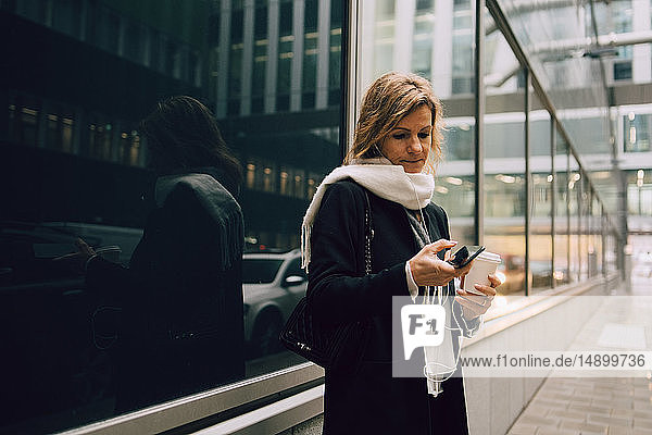 Businesswoman with coffee using smart phone while standing on sidewalk against modern building in city
