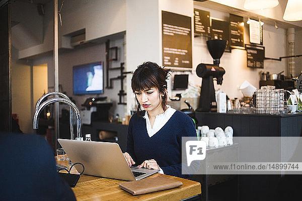 Selbstbewusste Unternehmerin mit Laptop am Tisch im Büro