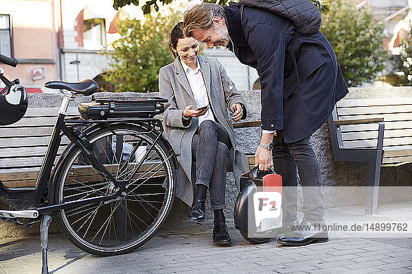 Smiling mature woman sitting on bench looking at man holding electric unicycle in city