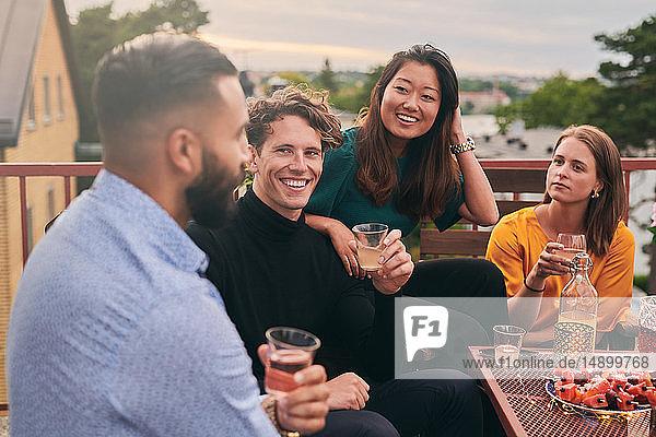 Fröhliche Freunde genießen das gesellige Beisammensein auf der Terrasse bei Sonnenuntergang