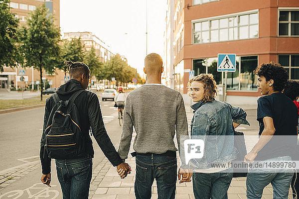 Rear view of male friends walking side by side on street in city