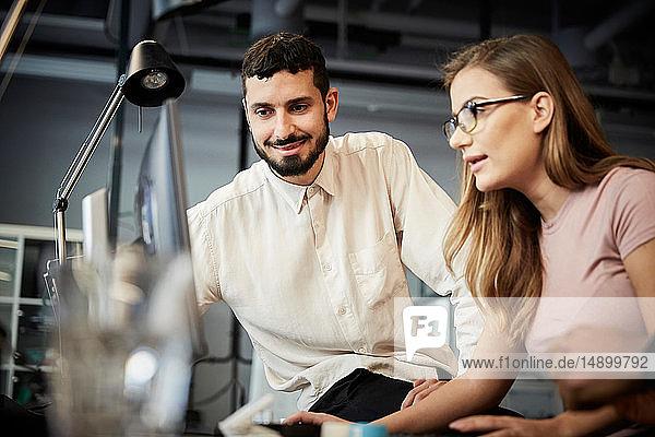Unternehmer und Unternehmerinnen  die bei Besprechungen im Büro auf den Computer schauen