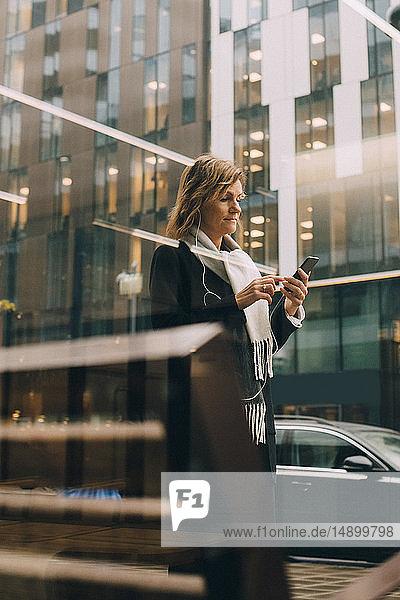 Seitenansicht einer Geschäftsfrau  die ein Mobiltelefon benutzt  während sie auf dem Bürgersteig gegen ein Gebäude in der Stadt läuft