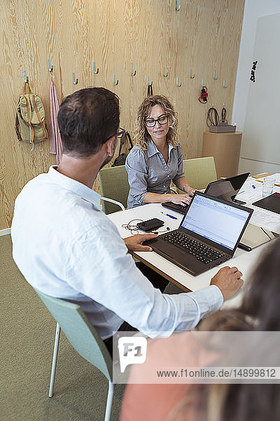 Businessman talking to female colleague while using laptop on conference table in board room