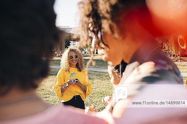Lächelnde Frau mit Freunden im Konzert an einem sonnigen Tag