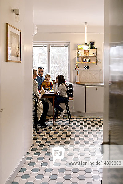 Family having meal together in kitchen seen through corridor at home