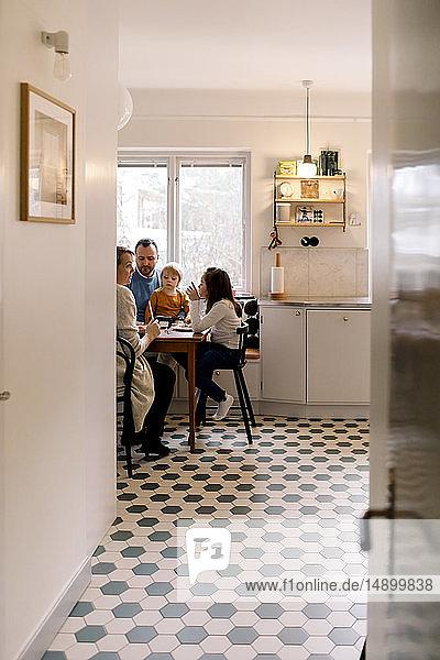 Familie beim gemeinsamen Essen in der Küche durch den Flur zu Hause gesehen
