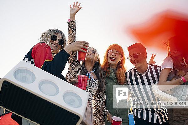 Glückliche Freunde mit Redner und Getränken beim Musikfestival gegen den Himmel