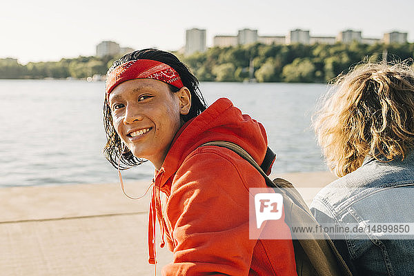 Portrait of smiling young man sitting by friend on promenade during sunny day