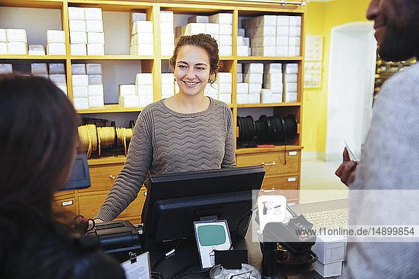 Lächelnde junge Kassiererin betrachtet Kundin  die im Möbelgeschäft steht
