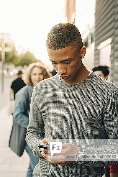 Teenage boy using mobile phone while standing on street in city